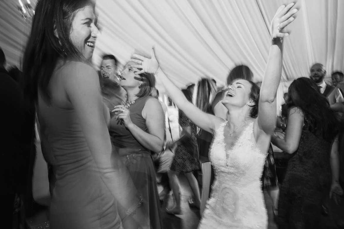The bride waves her arms on the air during the wedding party