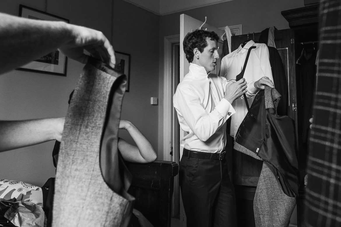 The groom puts on his suit