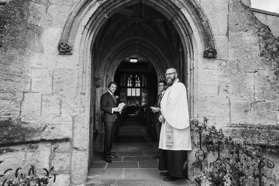 The vicar waits outside St Cyriacs church in Lacock