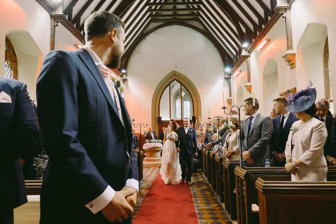 The groom waits as the bride arrives in the church