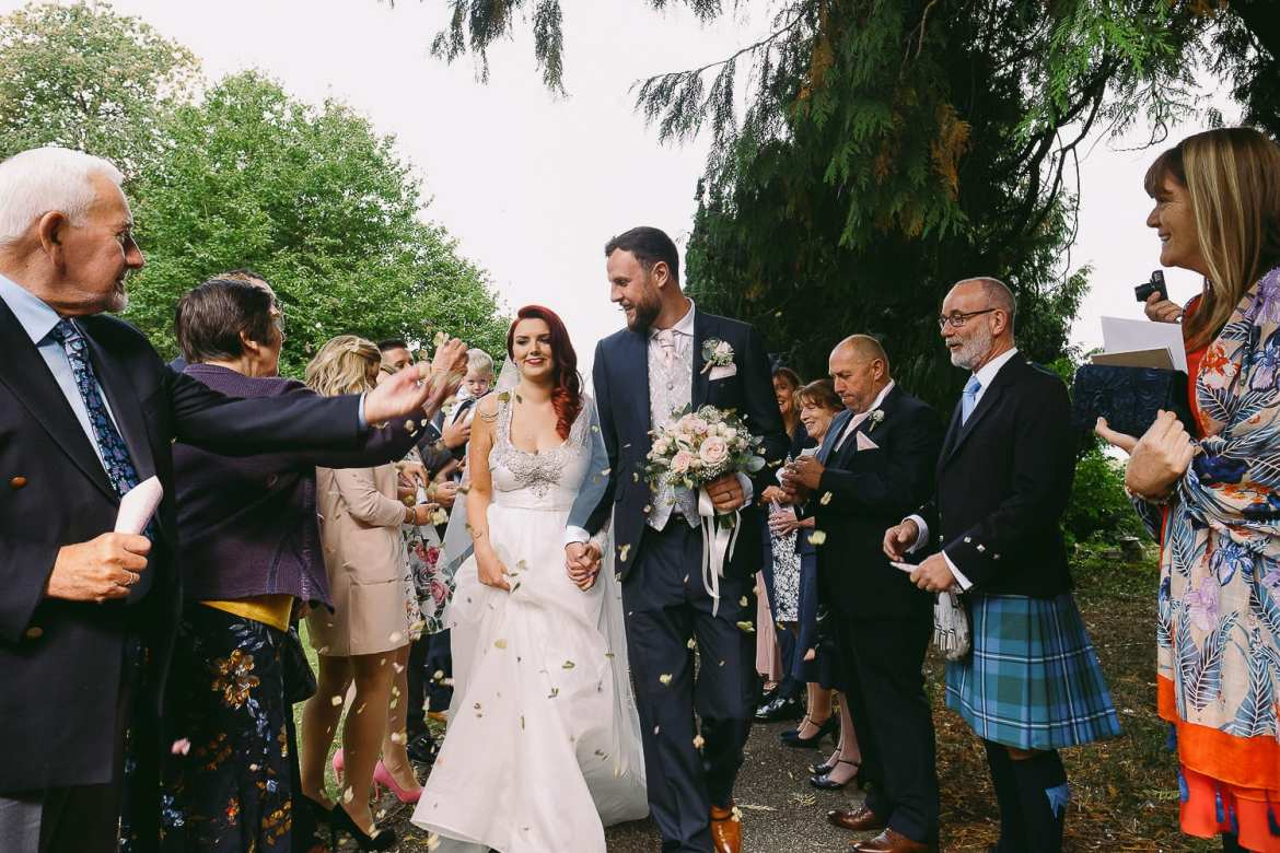 The guests throw confetti outside the church