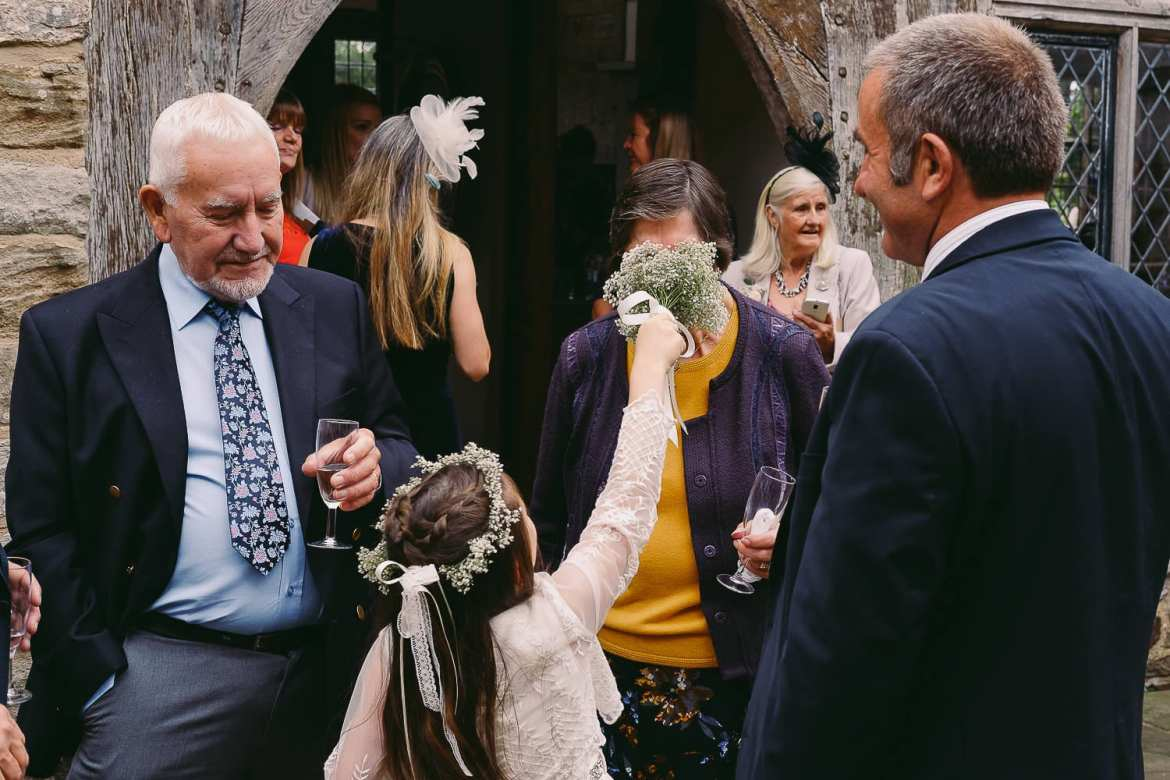 A flower girls shoves her flowers in her grandmas face