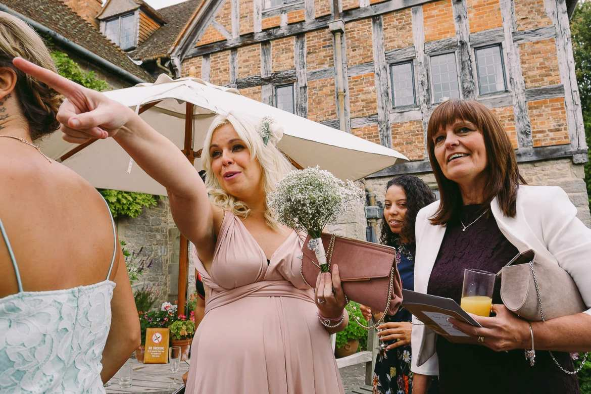 wedding guests and a bridesmaid pointing and laughing