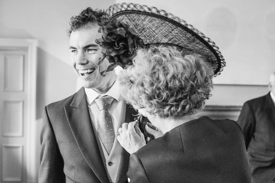 Groom having his buttonhole pinned on by mother of bride