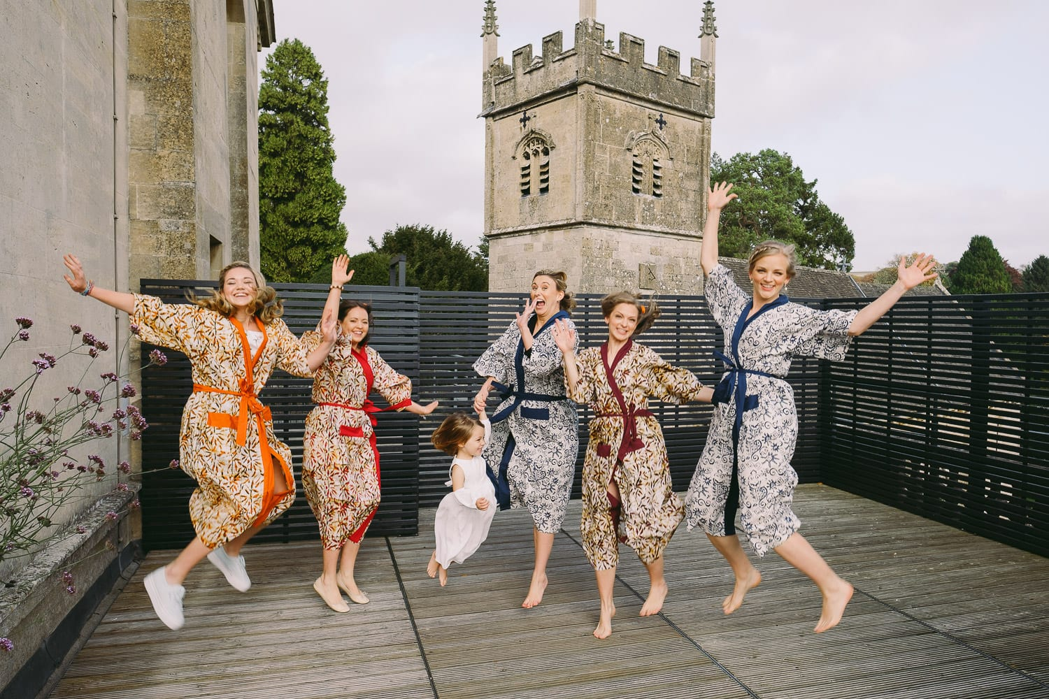 The bridal party jump in the air in front of St Mary's Church., Cowley