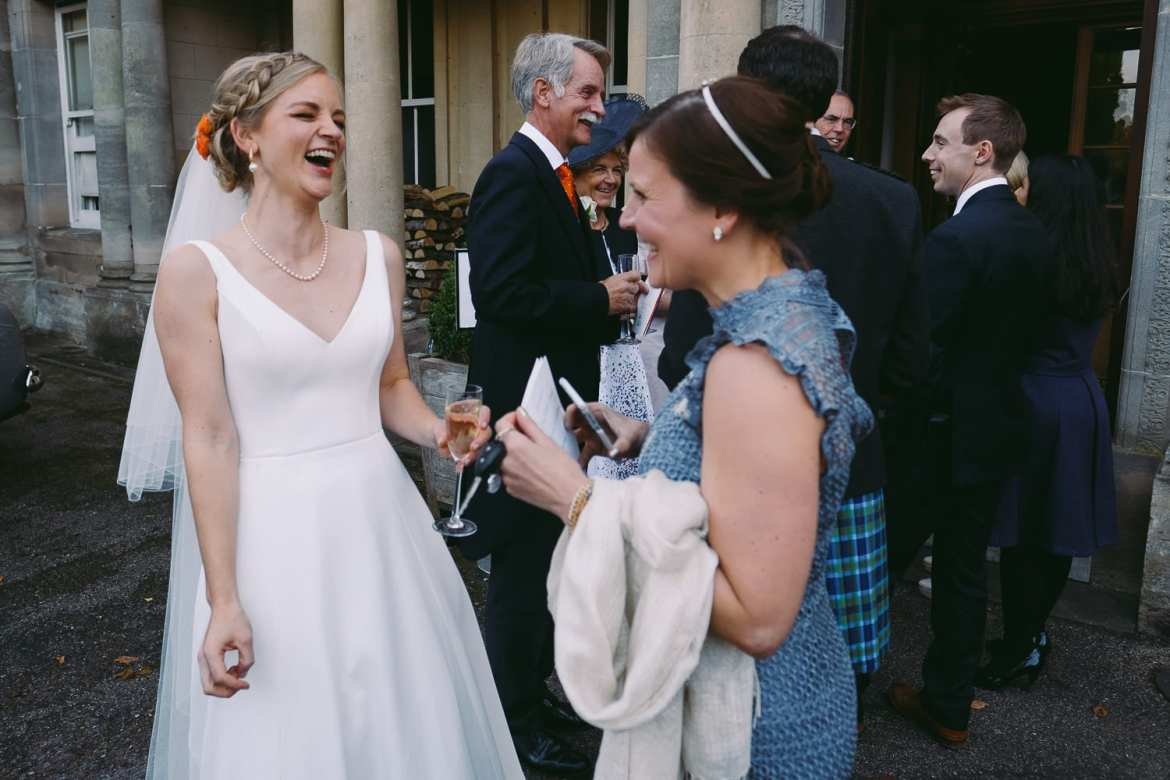 Bride laughing with friends in the receiving line