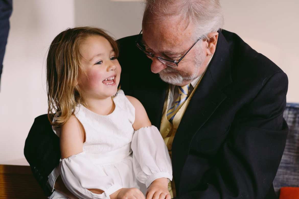 Flower girl sitting on grandads lap