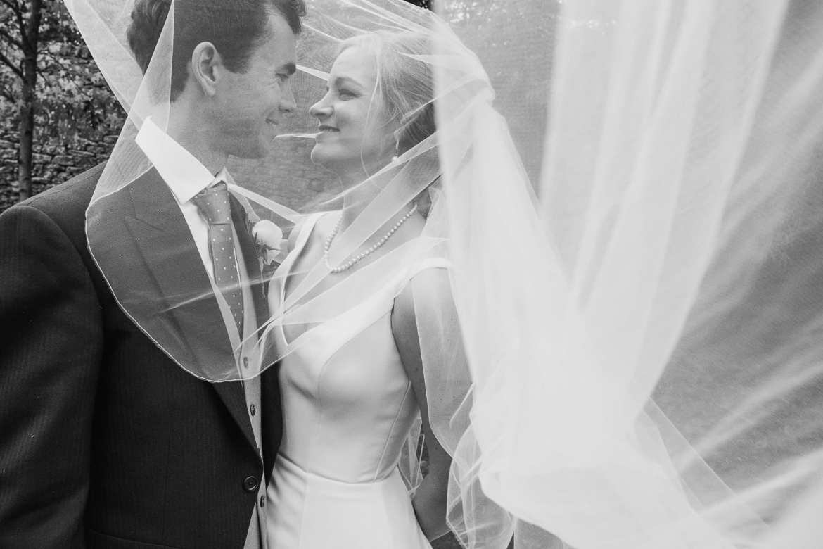 Black and white portrait of bride and groom through veil
