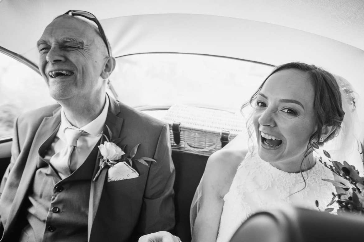 The bride and her dad rin the car on the way to the church