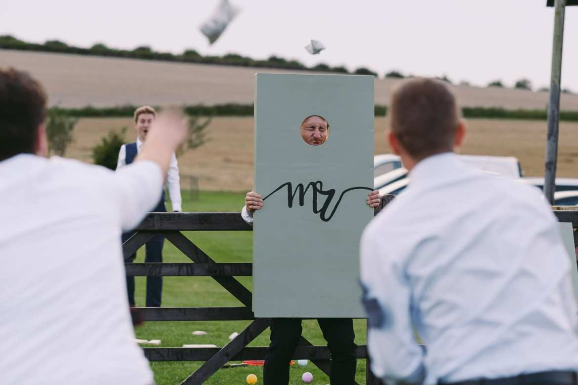 A guest holds up a target while the tothers throw beanbags at him