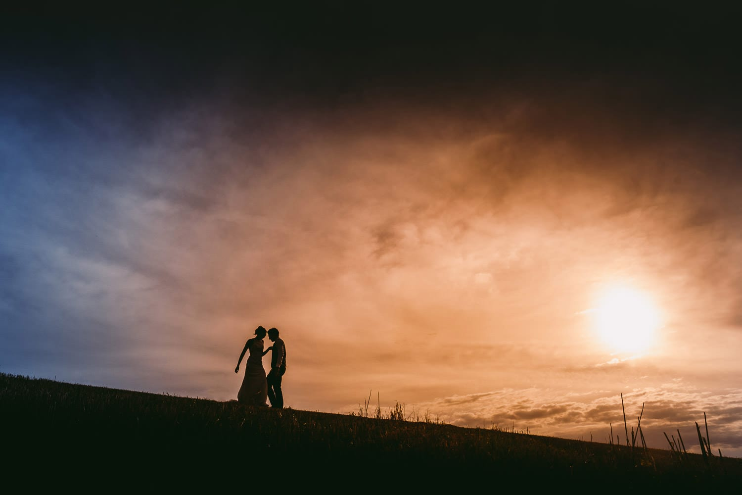 A Silhouette of the bride and groom at sunset