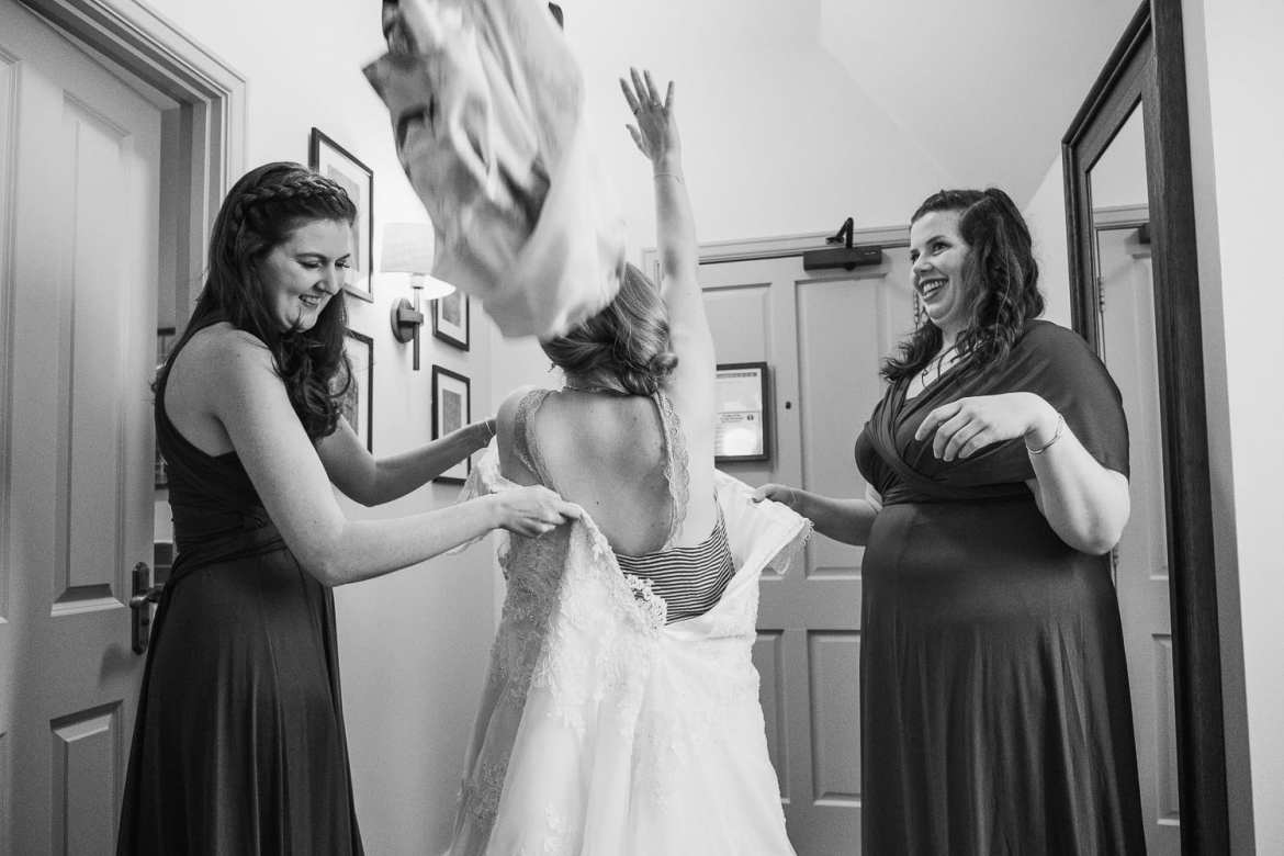 The bride throws off her top as she gets into her dress
