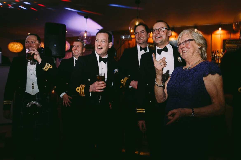 Wedding guests in black tie watch a wedding slideshow