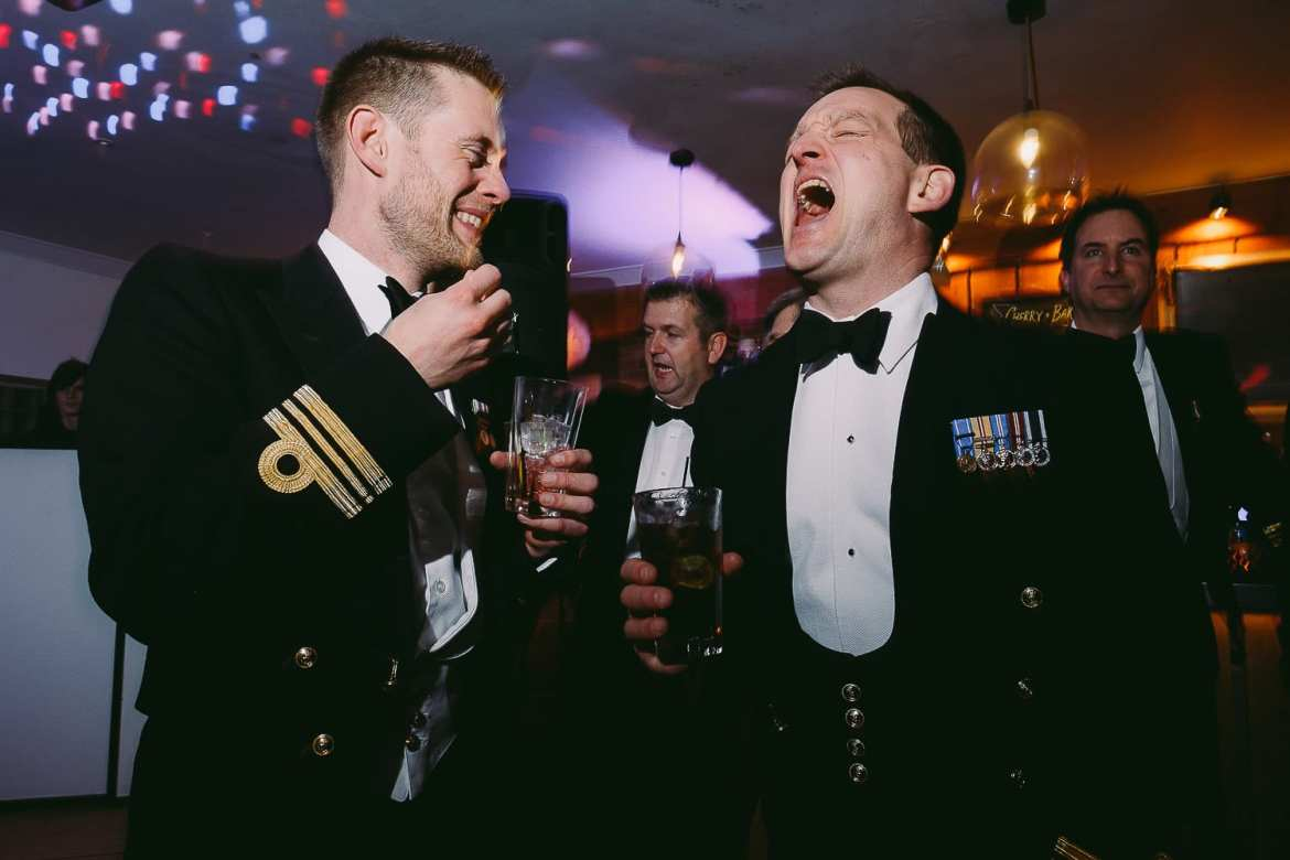 The groom and military guest laughing
