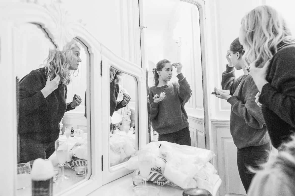 Bridesmaids doing their makeup in the mirror during the bridal prep