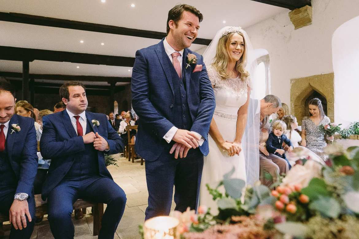 The bride and groom laughing during the ceremony in the Castle House