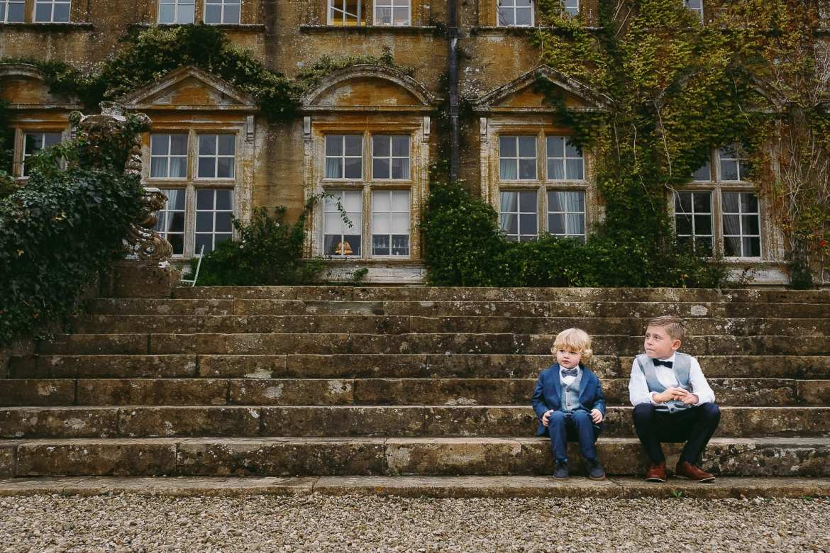 Pageboys sitting on the steps outside Brympton HOuse