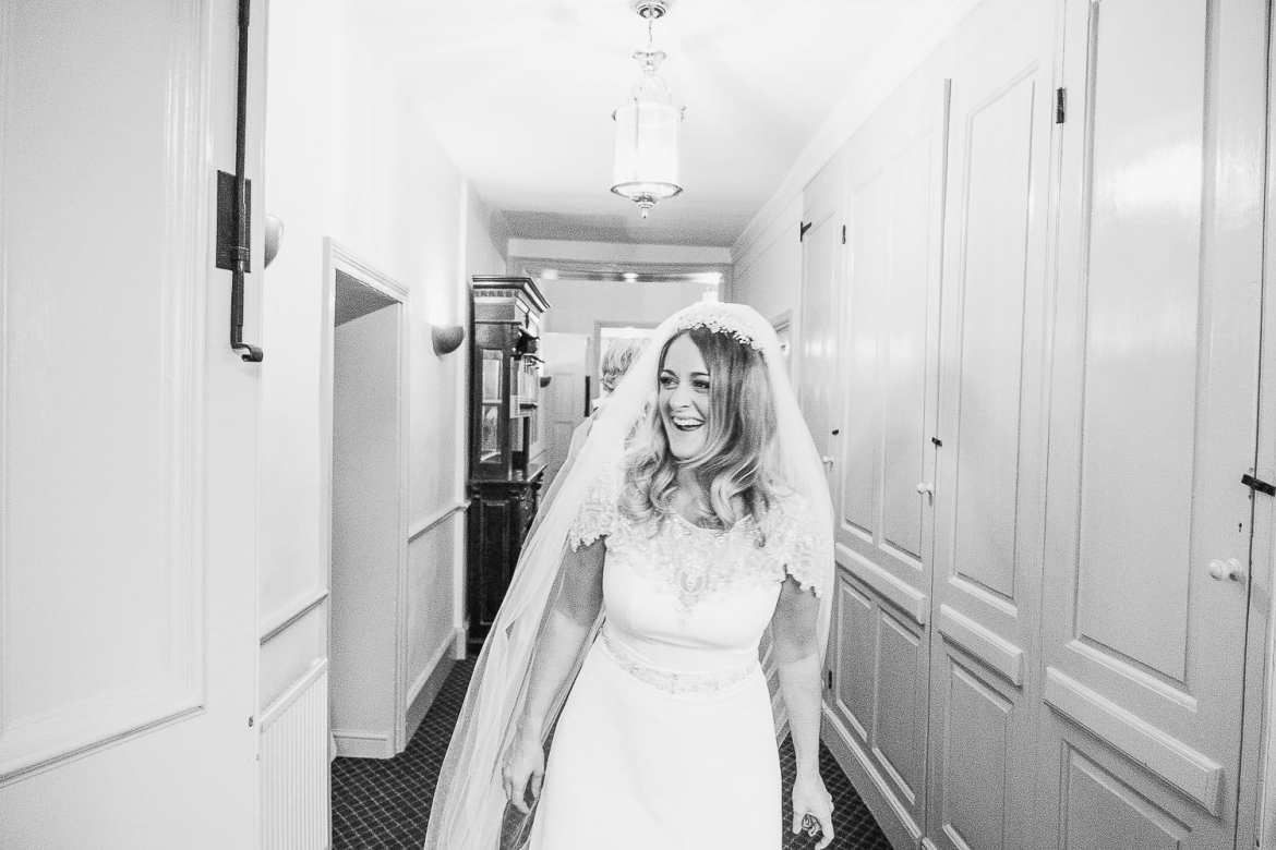 The bride laughing as she enters the ballroom for the wedding breakfast