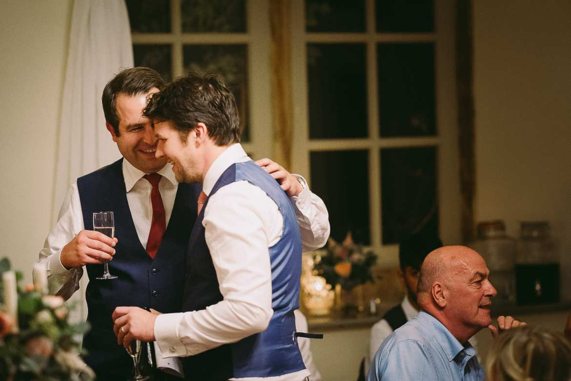 One of the best men pats the groom on the back