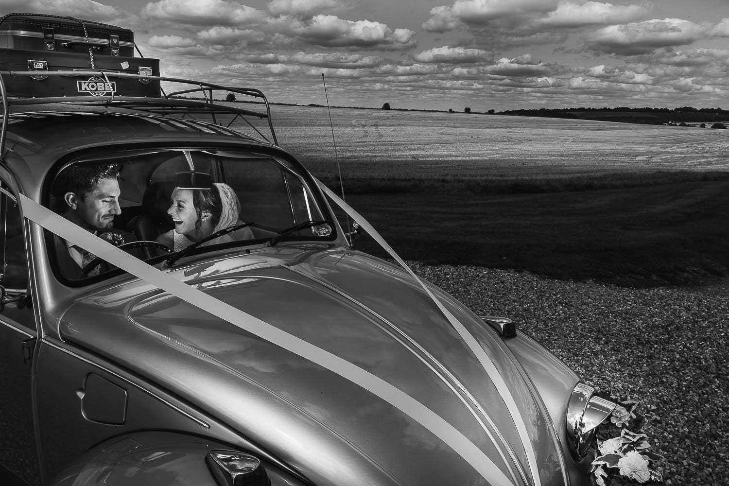 A portrait of the bride and groom in a beetle