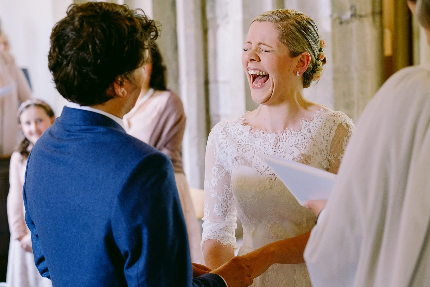 The bride laughing as the groom messes his words