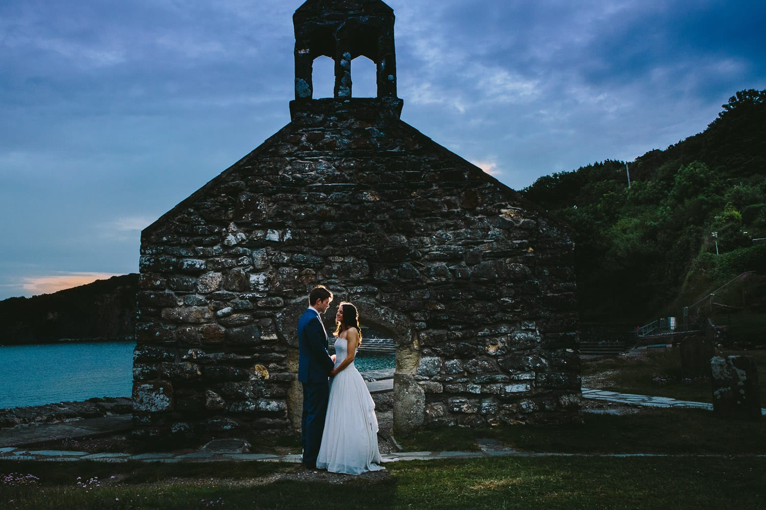 The bride and groom outside a ruined church