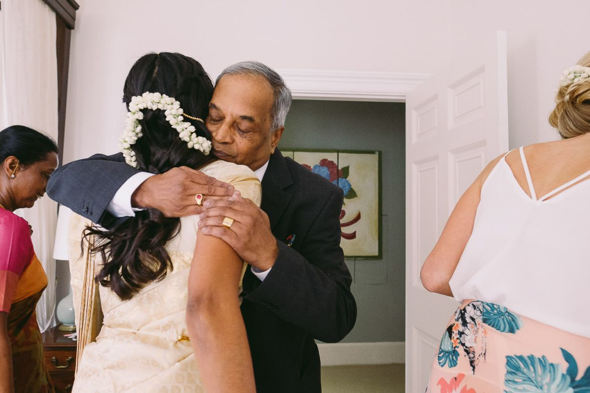 The bride's father hugs her