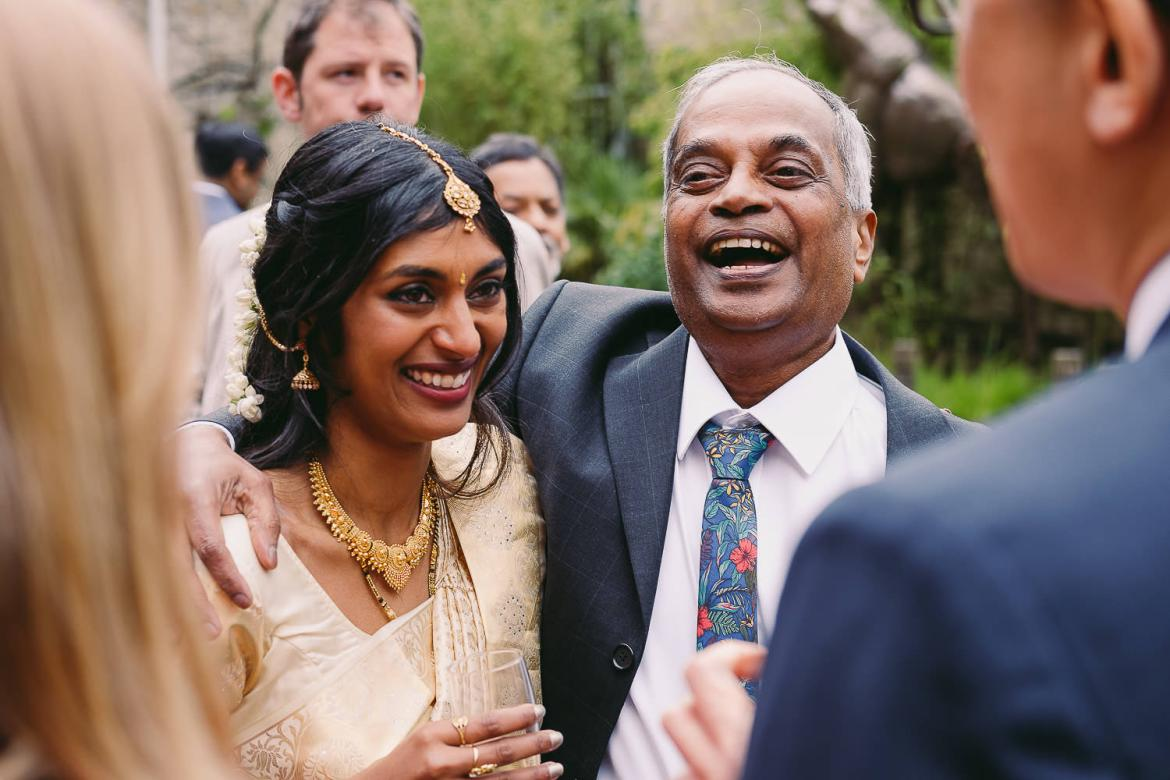 The father of the bride laughs and hugs his daughter
