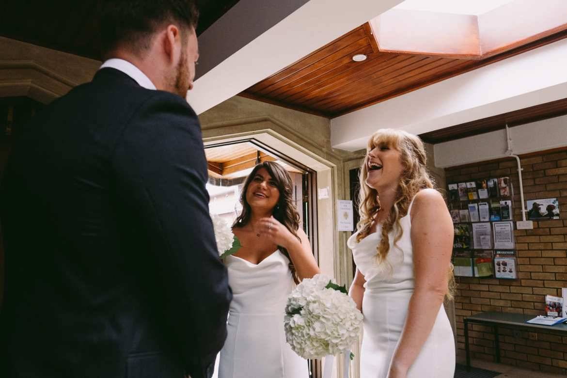 the bridesmaids laughing with a wedding guest