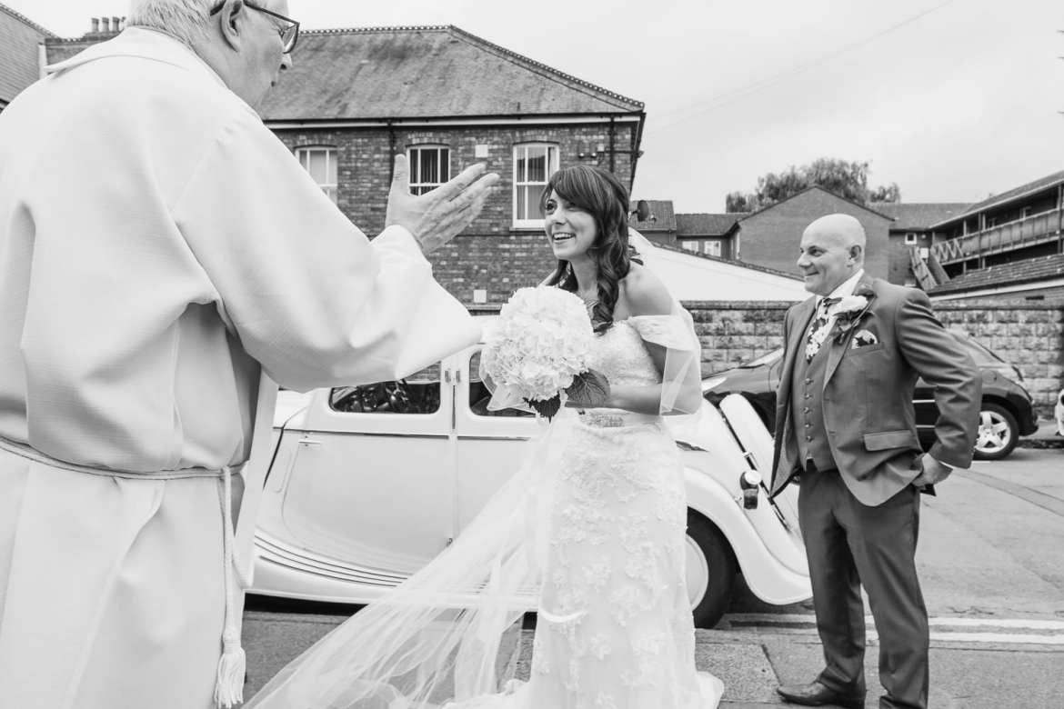 the bride looking excited, talks to the vicar