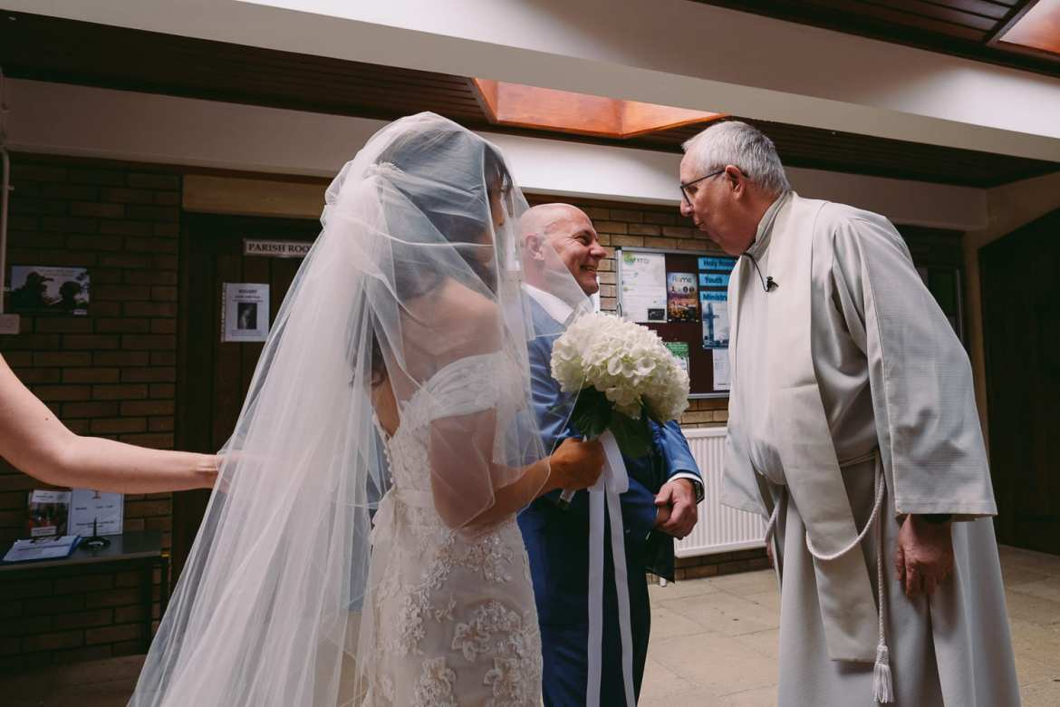 the father of the bride shares a joke with the vicar