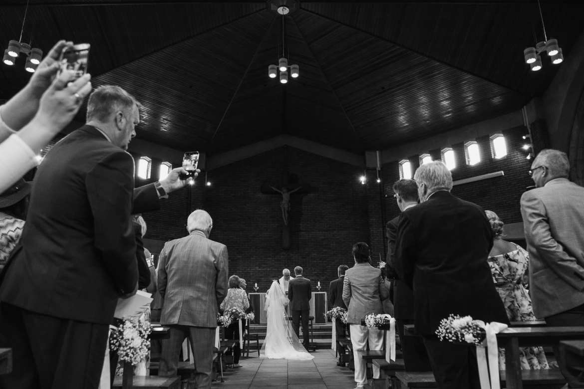 wedding guests take pictures on their phones of the couple at the altar