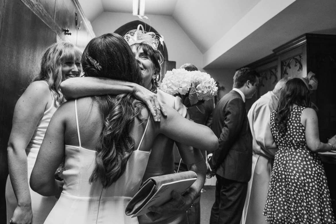 the mother of the groom hugs a bridesmaid