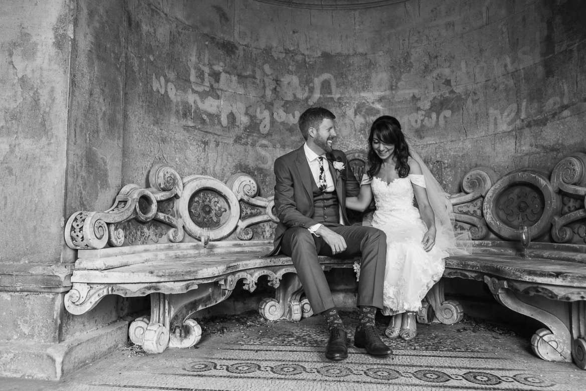 the bride and groom sitting on a bench laughing