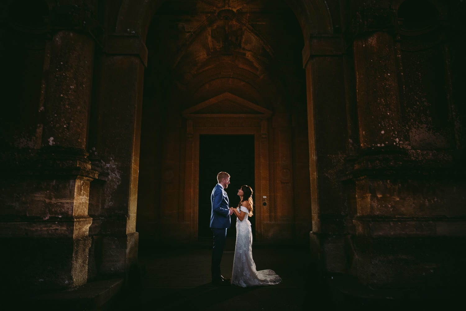 A portrait of the bride and groom in the grand entrance at Westonbirt House