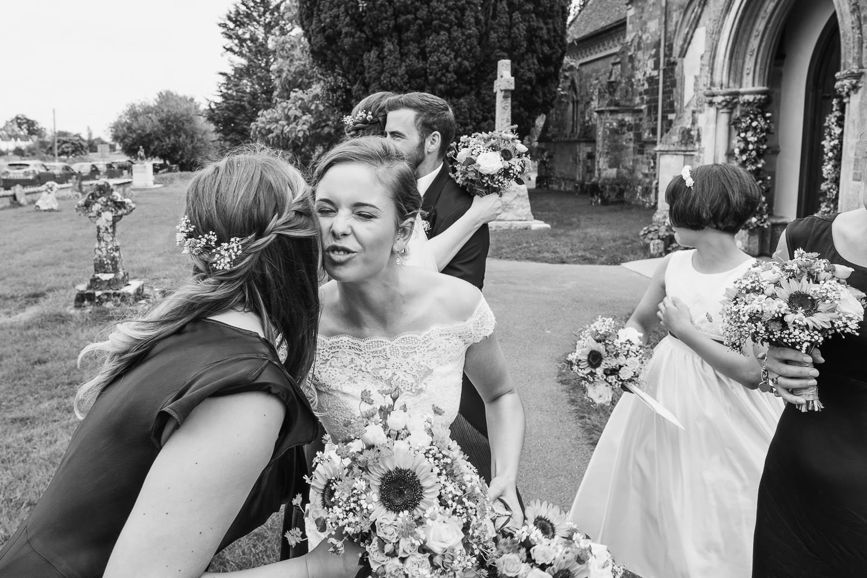 bride pulls a face as she air kisses a bridesmaid