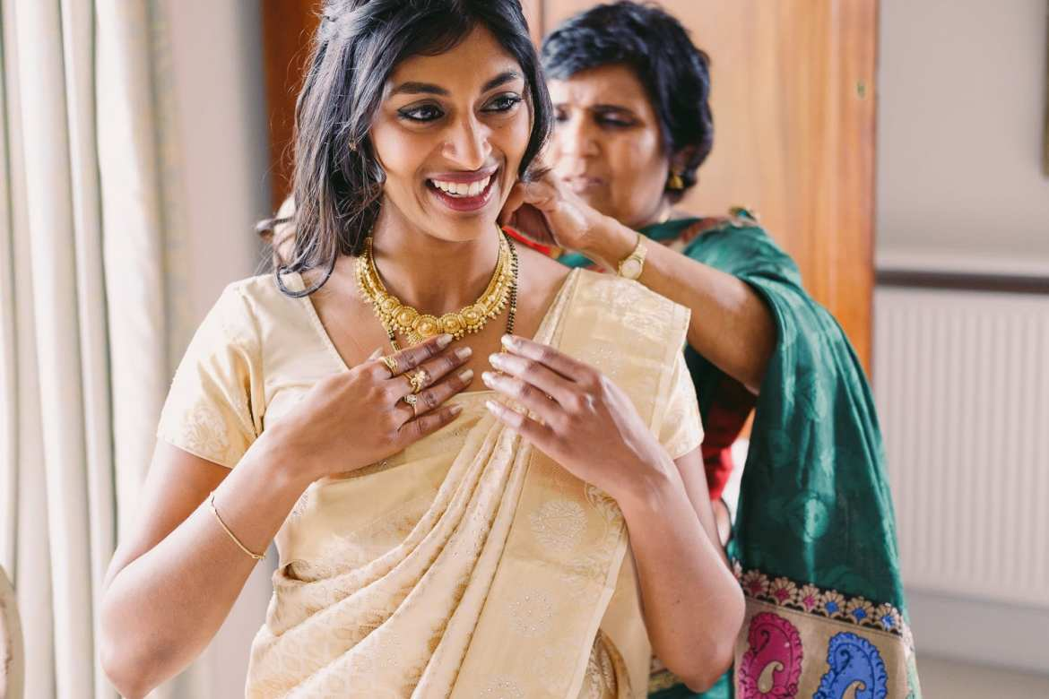 the bride is helped into her sari