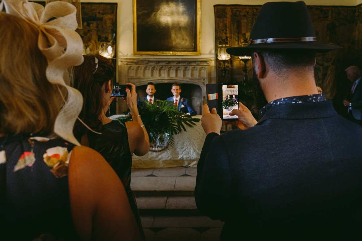 Wedding guests take pictures of the grooms