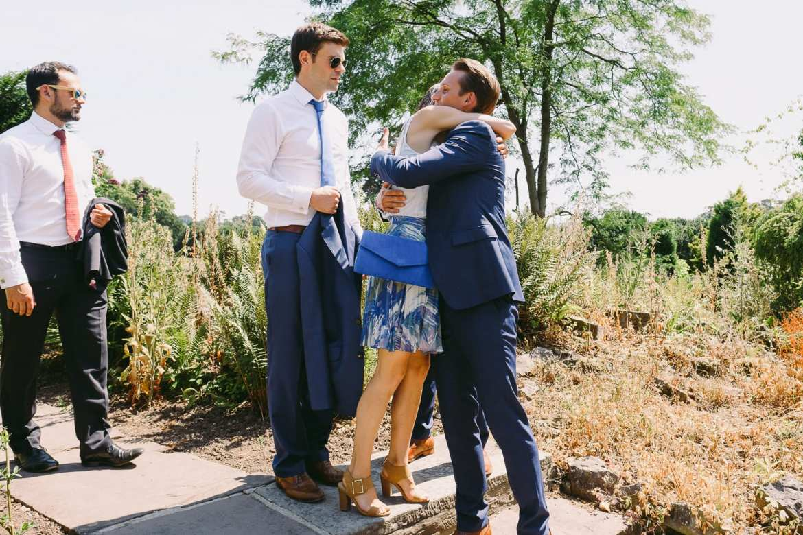 Guests hugging the grooms in the gardens