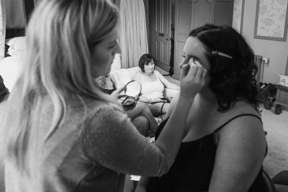 Mother of bride watching the make up artist with her daughter