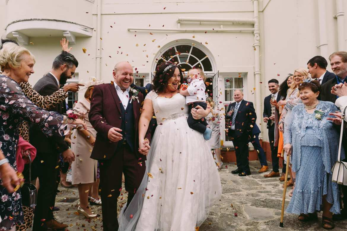 Bride and groom walk through confetti with their son