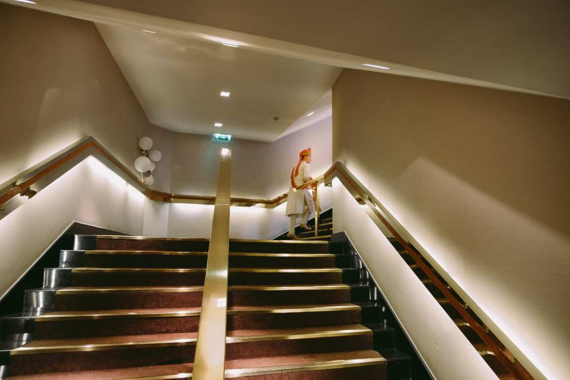 Groom on his way up the stairs in The Royal Garden Hotel
