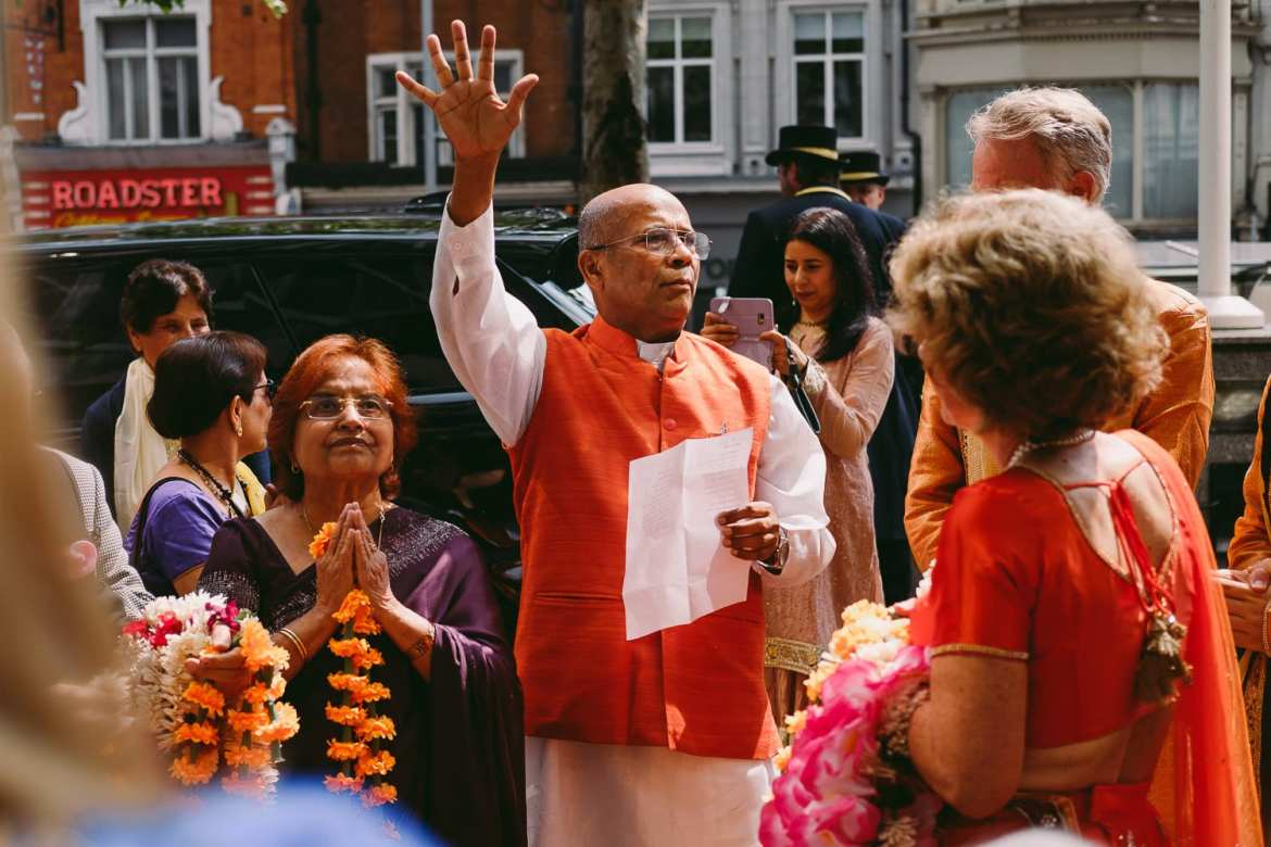 The priest welcomes everyone to the Indian wedding