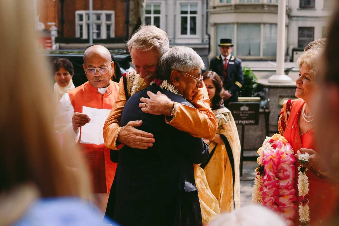 Fathers of the bride and groom exchange a hug