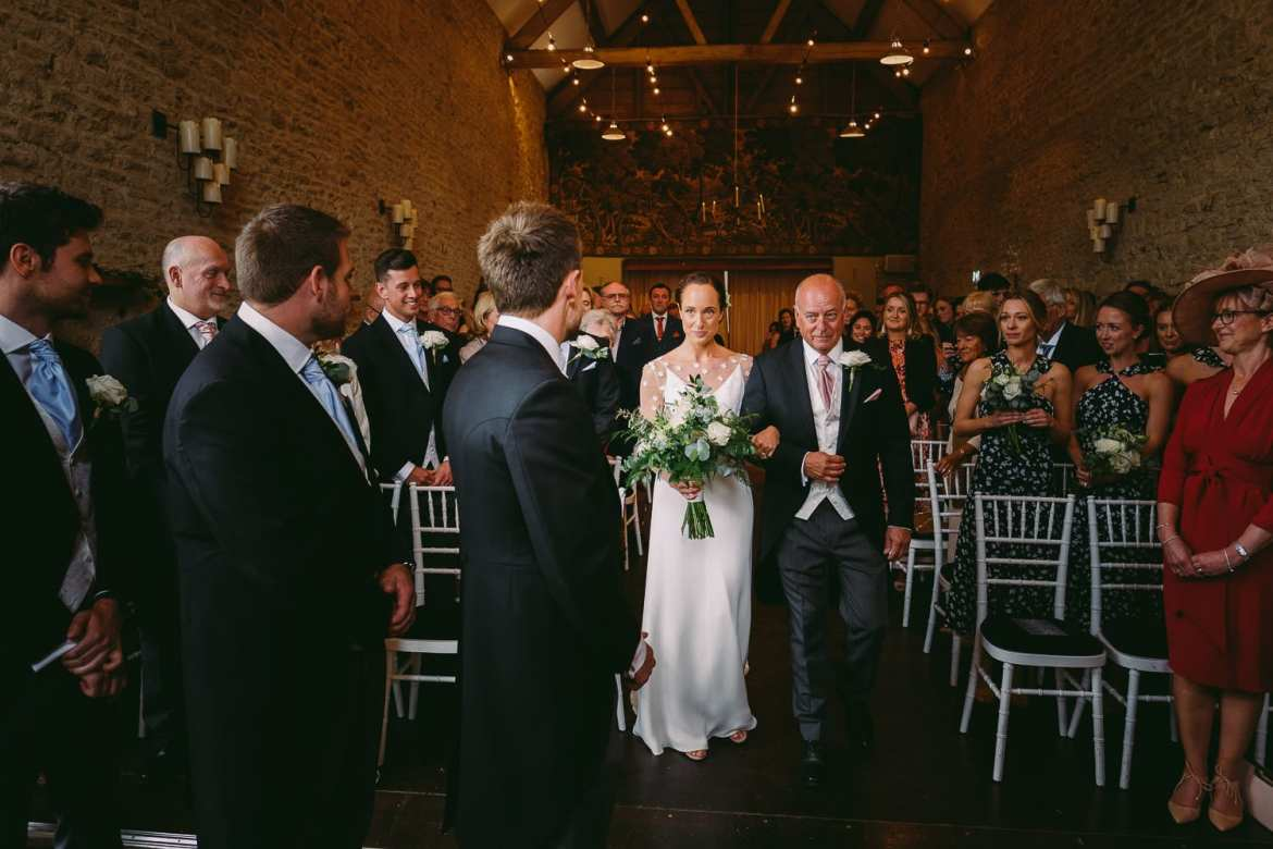 the groom talks to the guests in the stone barn