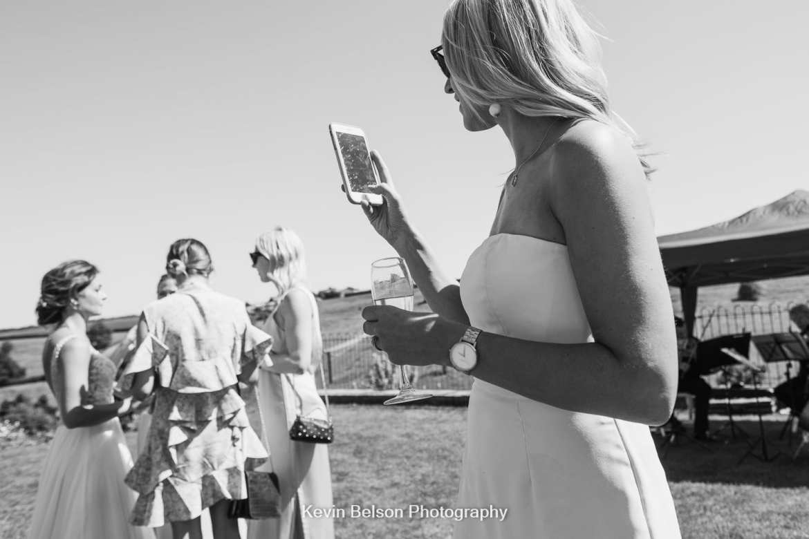 guest takes a picture of the bride
