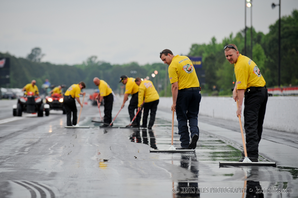 NHRA workers helps dry the track during a short rain delay on Saturday.