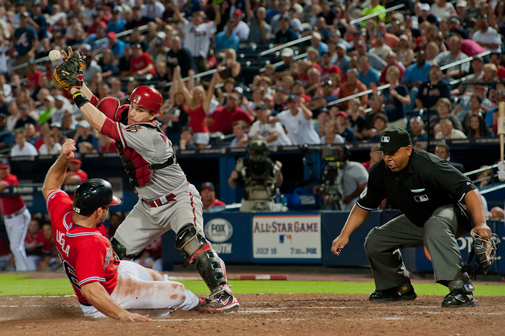 Arizona Diamondbacks catcher Miguel Montero misses the throw to tag Atlanta Braves short stop Dan Uggla out at home.