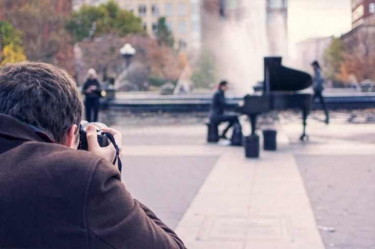 An image of a photographer outdoors taking a picture of a man playing a grand piano as people pass by near a fountain in a town square.
