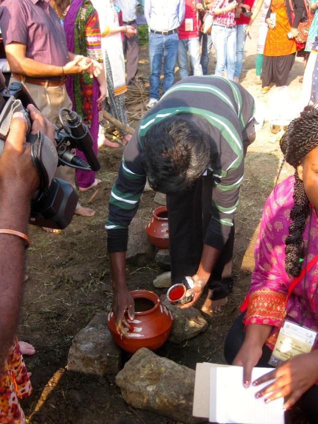 Adorning the clay pots with kola.
